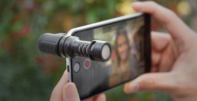 Manos sosteniendo un teléfono que tiene un microfono conectado